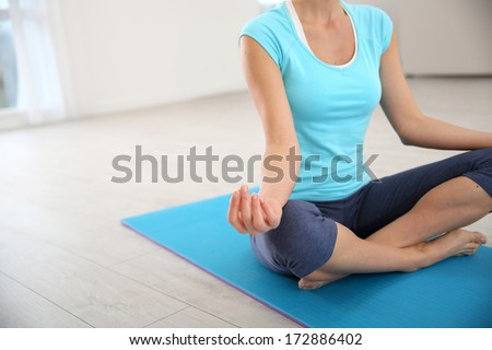 Focus on woman doing yoga exercises