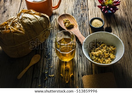 Focus Spot Chrysanthemum Tea and dried chrysanthemum on an old wooden table. Chrysanthemum blossoms are a type of herbal plants. In the morning, drink chrysanthemum Tea will make you feel refreshed.