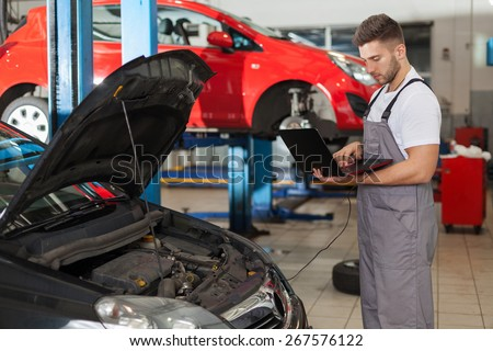 Focused auto mechanic working on a computer connected to a car engine - stock photo