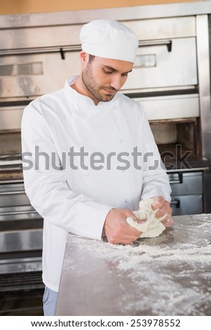 Focused baker kneading dough at counter in the kitchen of the bakery
