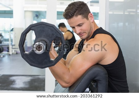Focused bodybuilder lifting heavy black dumbbell at the gym - stock photo