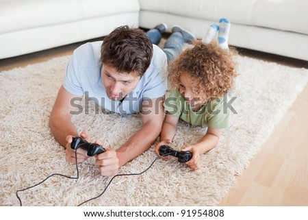 Focused boy and his father playing video games while lying on a carpet - stock photo