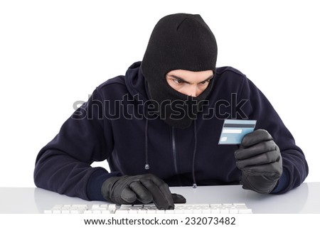 Focused burglar using computer and debit card on white background - stock photo