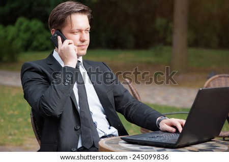 Focused businessman. Attractive young caucasian man in formal wear working on laptop while sitting at the table outdoors. - stock photo