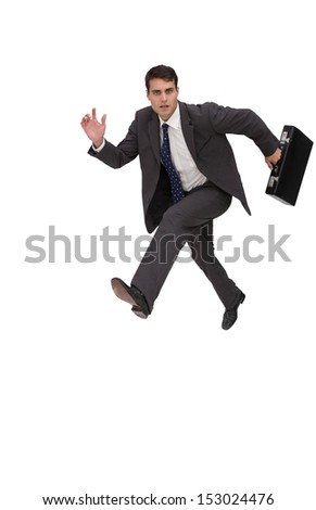Focused businessman holding a briefcase and running on white background