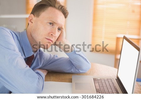 Focused businessman looking at laptop in his office
