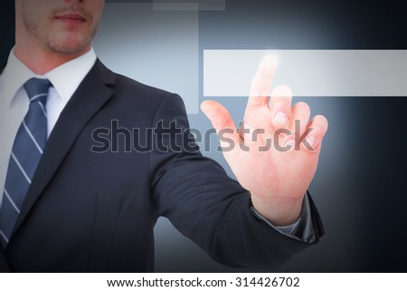 Focused businessman pointing with his finger against blue background