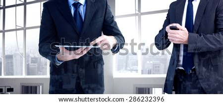 Focused businessman texting on his mobile phone against airport terminal - stock photo