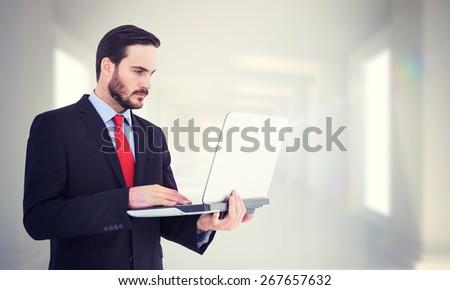 Focused businessman using his laptop against digitally generated room - stock photo