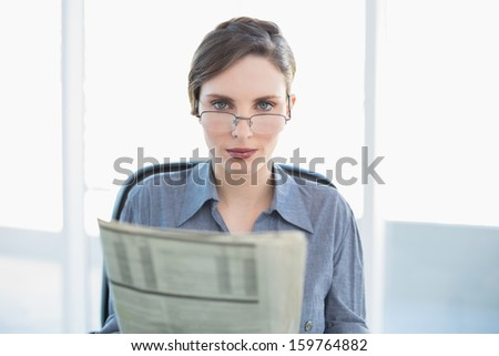 Focused businesswoman holding newspaper sitting at her desk looking at camera - stock photo