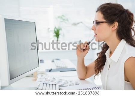 Focused businesswoman with glasses using computer in the office - stock photo