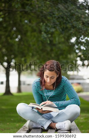 Focused casual student sitting on bench reading on campus at college - stock photo