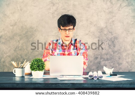 Focused caucasian male looking at laptop on wooden office desk with various items on concrete wall background. Frontview - stock photo