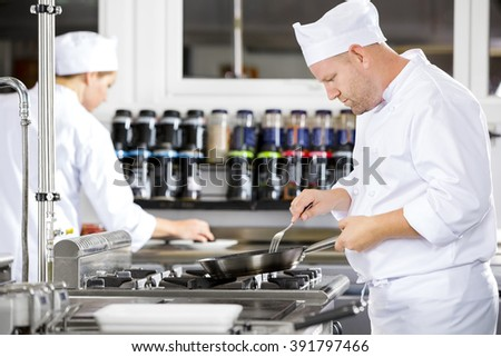 Focused chefs makes food in professional kitchen - stock photo
