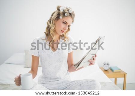 Focused cute blonde wearing hair curlers reading newspaper sitting on cozy bed - stock photo