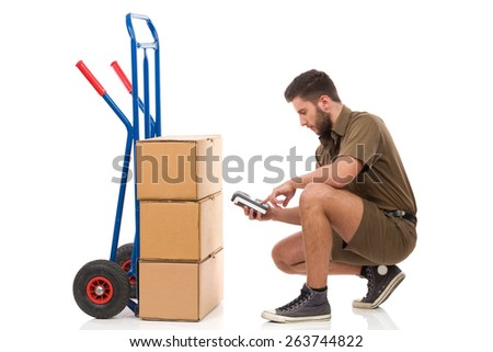 Focused delivery man crouching close to carton box and holding digital equipment. Full length studio shot isolated on white. - stock photo