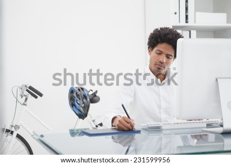 Focused designer drawing on digitizer in his office