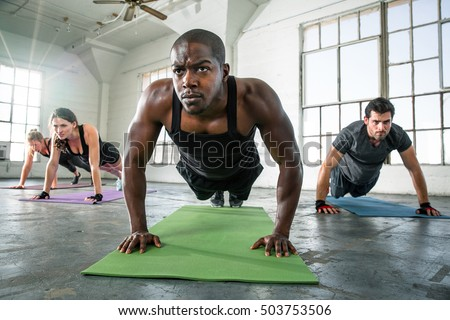 Focused determined powerful strong male fitness trainer exercising push ups