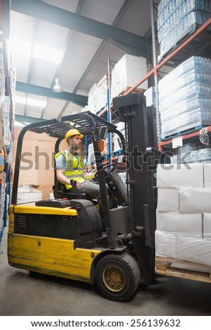 Focused driver operating forklift machine in warehouse - stock photo