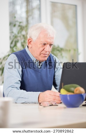 Focused elderly man using laptop to his work - stock photo