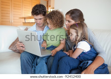 Focused family using a laptop in their living room - stock photo
