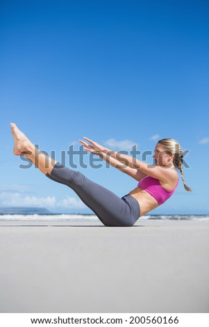 Focused fit blonde doing yoga on the beach on a sunny day - stock photo