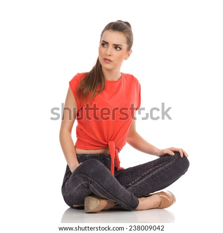Focused girl in red top, black jeans is sitting on the floor with legs crossed and looking away. Full length studio shot isolated on white. - stock photo