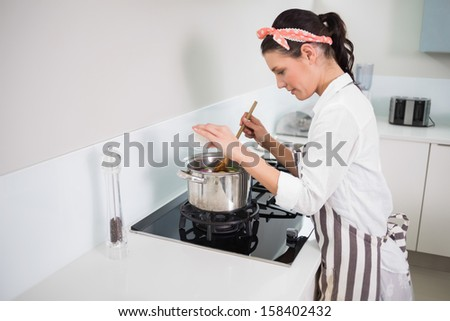Focused gorgeous cook mixing vegetables in bright kitchen - stock photo