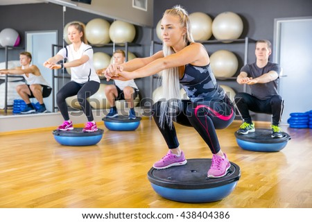 Focused group training squats on half ball at fitness gym - stock photo
