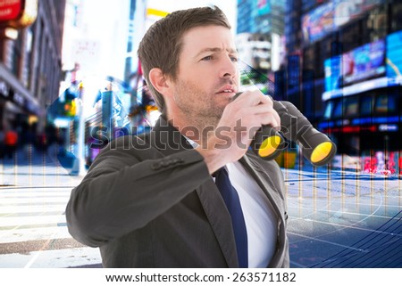 Focused handsome businessman holding binoculars against global business graphic in blue