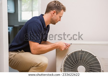 Focused handyman fixing air conditioning in a new house - stock photo