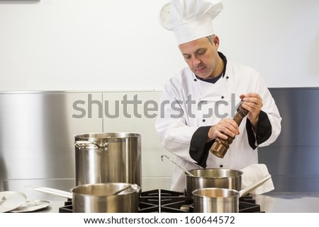 Focused head chef using pepper mill in professional kitchen - stock photo