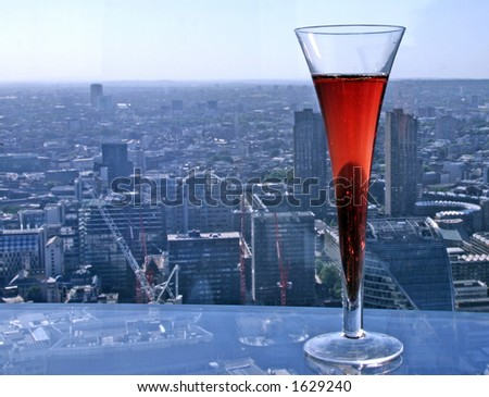 Focused Kir Royal cocktail with slightly blurry aerial view of London - stock photo