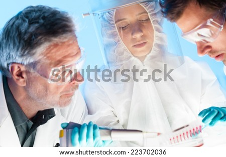 Focused life science professionals pipetting cell colonies containing media into the petri dish monitoring their growth. - stock photo
