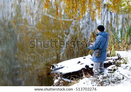 Focused male angler in the usual jacket and hat throwing the spinner bait on the shore of winter pond with snow under trees and leaves of autumn birches on the branches with reflection in the water.