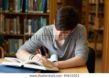 Focused male student working in a library - stock photo