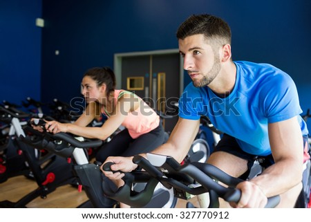Focused man and woman on exercise bikes at the gym - stock photo
