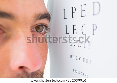 Focused man on eye test letters on white background
