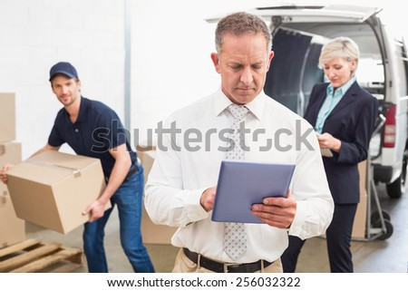 Focused manager holding tablet in front of his colleagues in a large warehouse