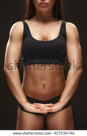 Focused on result. Cropped studio shot of a fit female athlete stretching her hands on black background. - stock photo
