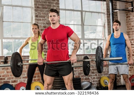Focused people lifting barbell at the gym - stock photo