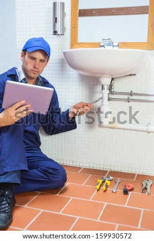 Focused plumber consulting tablet in public bathroom - stock photo