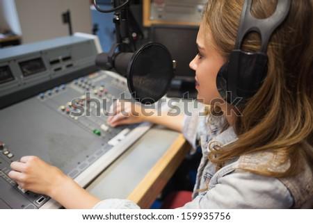Focused pretty radio host moderating sitting in studio at college - stock photo