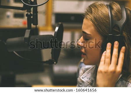 Focused pretty singer recording a song in studio at college - stock photo