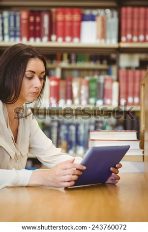 Focused pretty student using tablet computer in library - stock photo