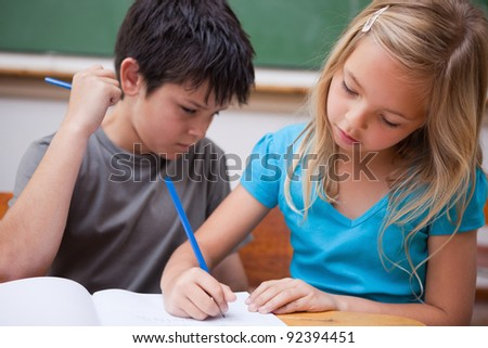 Focused pupils working together in a classroom - stock photo