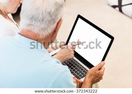 Focused senior couple using laptop at home - stock photo
