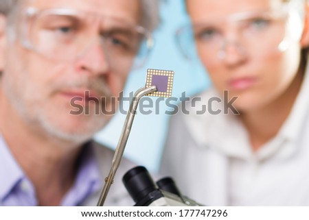 Focused senior  engineer holding and showing the micro chip to his student.  Lens focus on the chip. - stock photo