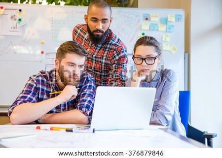 Focused serious multiethnic group of young people sitting and working with one laptop together - stock photo