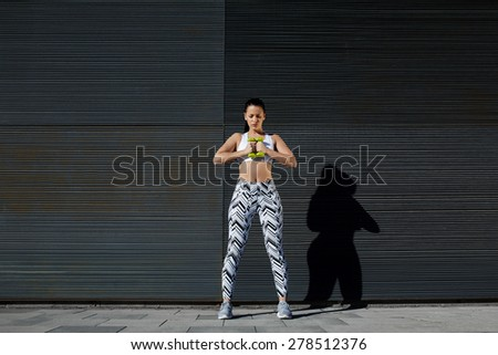 Focused sporty woman using dumbbells to work out her arms while training outdoors against black copy space wall for your text message, female in workout gear holding weights with her hands together - stock photo